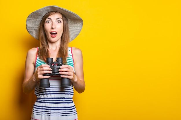 Jonge vrouw in shock, verrast, in een hoed en gestreepte jurk houdt een verrekijker op een gele ruimte.