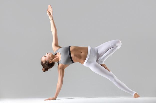 Jonge vrouw in side plank poseren, grijze studio achtergrond