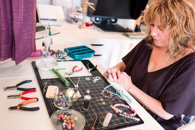 Jonge vrouw in sieraden grootte sieraden maken met polymeerklei.
