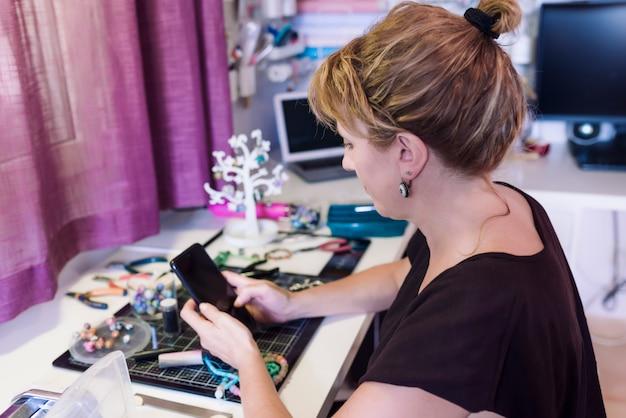 Jonge vrouw in sieraden workshop een bericht schrijven op haar mobiele telefoon