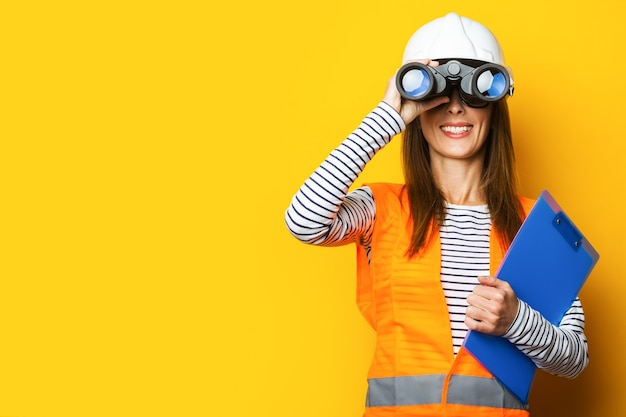 Jonge vrouw in signaalvest en bouwhelm die door een verrekijker op geel kijkt