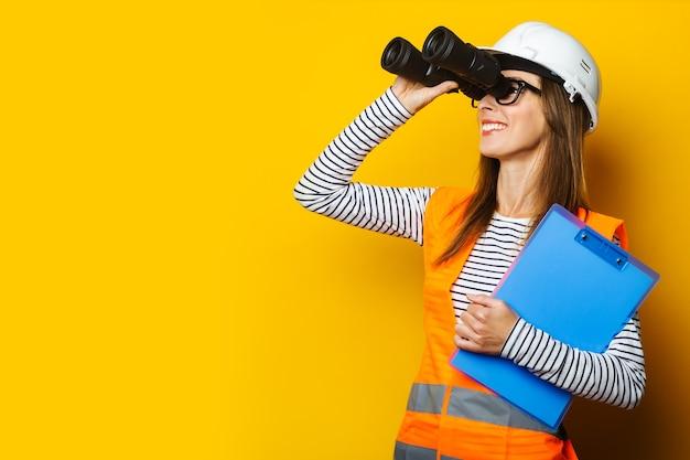 Jonge vrouw in signaalvest en bouwvakker houdt klembord vast en kijkt door een verrekijker op geel