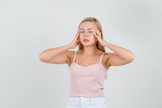 Jonge vrouw in singlet, minirok met hoofdpijn