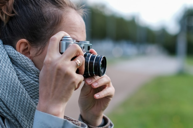 Jonge vrouw in sjaal die foto's met retro fotocamera neemt op straat.