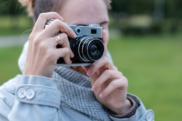 Jonge vrouw in sjaal, mantel nemen van foto's met retro fotocamera op straat.