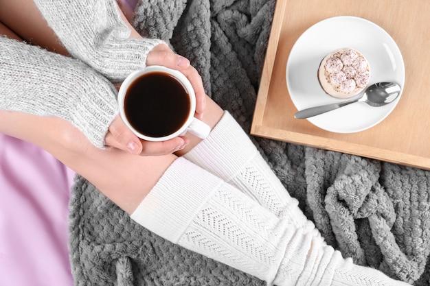 Jonge vrouw in sokken op bed met kop koffie