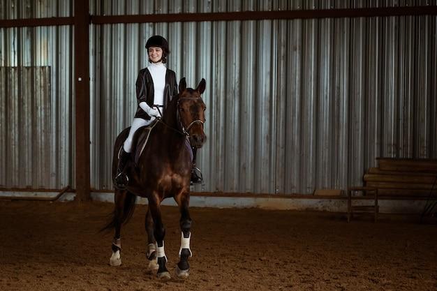 Jonge vrouw in speciaal uniform en helm rijpaard. paardensport