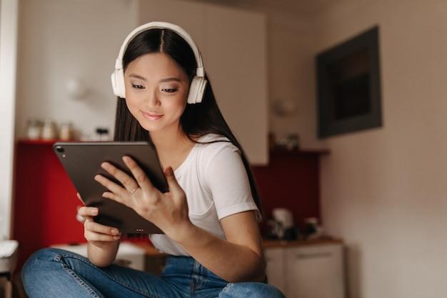 Jonge vrouw in spijkerbroek en wit t-shirt onderzoekt tablet en luistert naar muziek in de koptelefoon