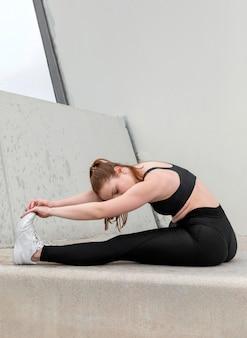 Jonge vrouw in sportkleding buitenshuis oefenen