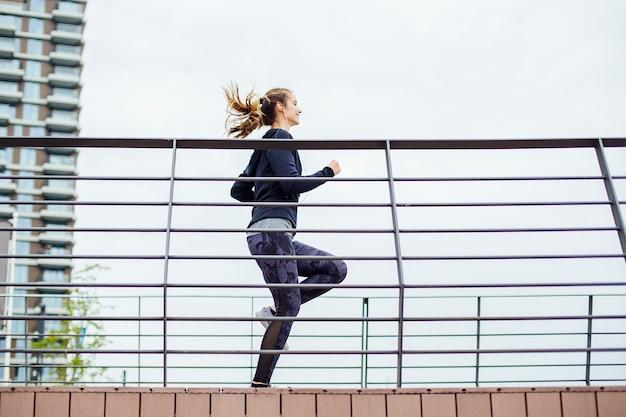 Jonge vrouw in sportkleding die op de brug door de rivier loopt