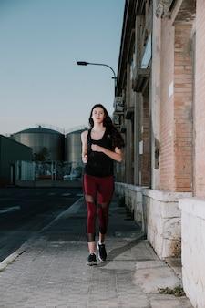 Jonge vrouw in sportkleding die op straat loopt