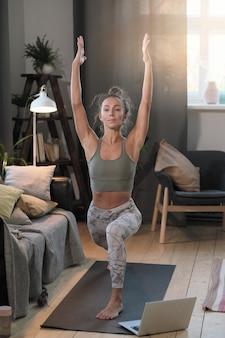 Jonge vrouw in sportkleding doen rekoefeningen tijdens de training in de kamer thuis
