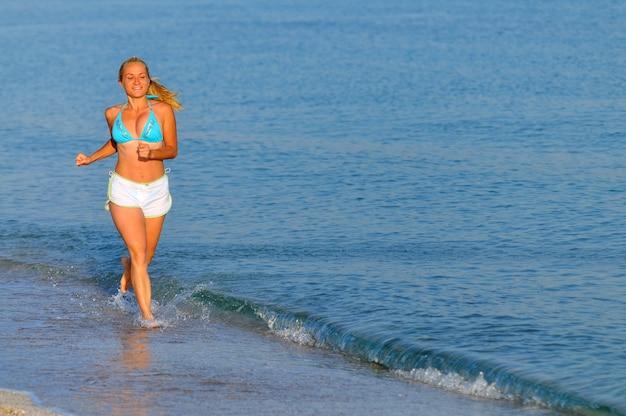 Jonge vrouw in sportkleding en sneakers die in de buurt van nog zee loopt