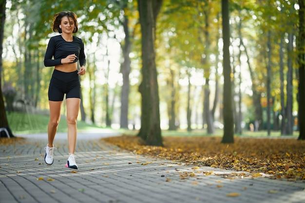Jonge vrouw in sportkleding en sneakers joggen in het park