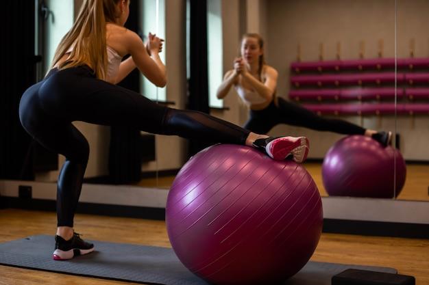 Jonge vrouw in sportkleding is bezig met fitball in de sportschool