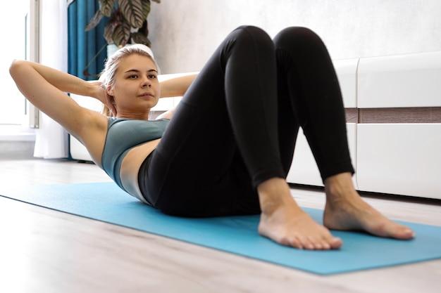 Jonge vrouw in sportkleding schudt de pers op de vloer van het huis