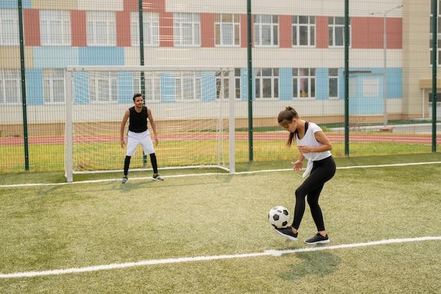Jonge vrouw in sportkleding staande op voetbalveld tijdens het leren spelen met sportman