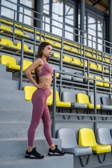 Jonge vrouw in sportkleding zit op een stadionstoel en resr na ochtendoefening
