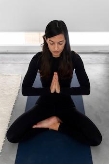Jonge vrouw in sportkleding zittend in lotus houding met namaste handen en mediteren tijdens yoga praktijk thuis