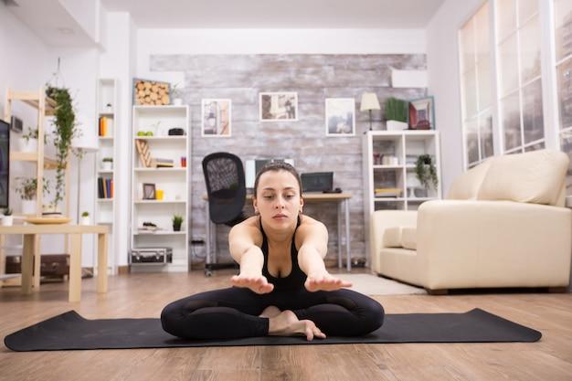 Jonge vrouw in sportkleding zittend op lotus yoga pose die zich naar voren uitstrekt in huis.