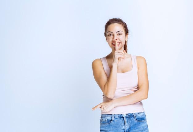 Jonge vrouw in sportshirt die om stilte vraagt