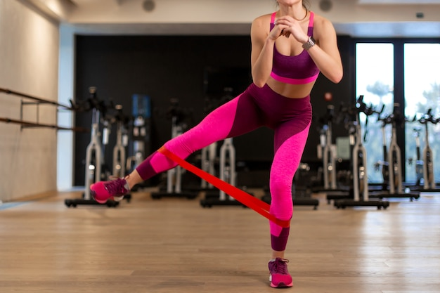 Jonge vrouw in sportwear sportoefening met geschikt elastiekje op benen in gymnastiek. fitness en wellness levensstijl concept