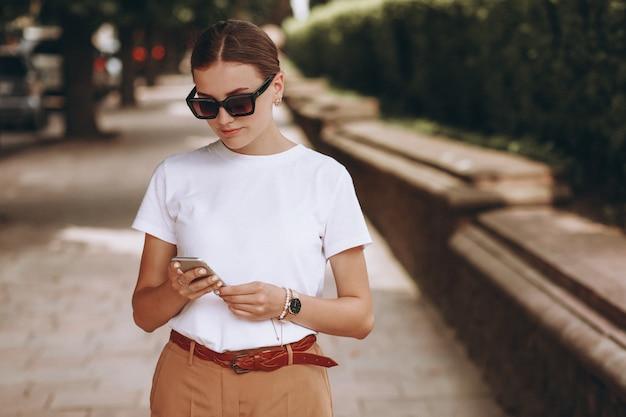 Jonge vrouw in stadscentrum die op telefoon spreekt
