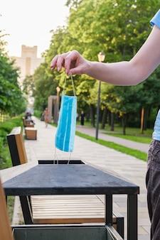 Jonge vrouw in stadspark nadert vuilnisbak en zet blauw medisch beschermend masker af