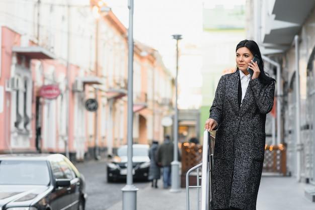 Jonge vrouw in stijlvolle kleding in de stad