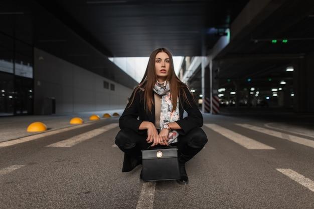 Jonge vrouw in stijlvolle lente slijtage met zijden vintage sjaal met mode lederen handtas poseren op de weg buitenshuis. het leuke meisjesmodel zit op de stoep. trendy dameskleding en accessoires.
