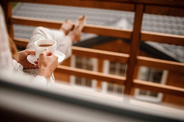 Jonge vrouw in stijlvolle nachtkleding geniet van het drinken van koffie of thee buiten op het balkon in de ochtend en kijkt naar de bergen.