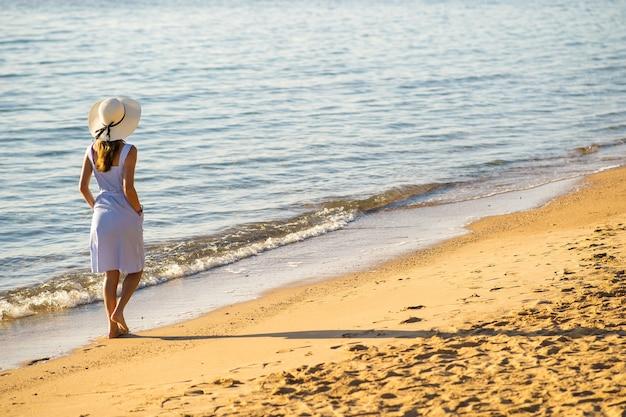 Jonge vrouw in strohoed en een jurk die alleen loopt op een leeg zandstrand aan de kust. eenzaam toeristenmeisje dat horizon over kalm oceaanoppervlak bekijkt op vakantiereis.