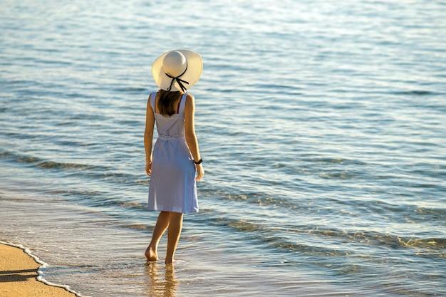 Jonge vrouw in strohoed en een jurk die alleen staat op een leeg zandstrand aan de kust. eenzaam toeristenmeisje dat horizon over kalm oceaanoppervlak bekijkt op vakantiereis.