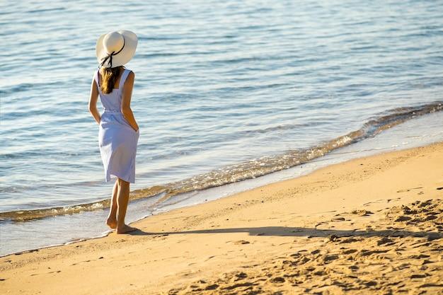 Jonge vrouw in strohoed en een kleding die alleen op leeg zandstrand op overzeese kust lopen