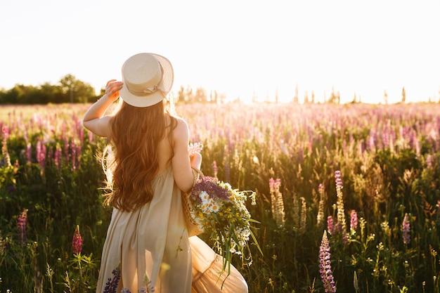 Jonge vrouw in strohoed en kleding met boeket van lupinebloemen