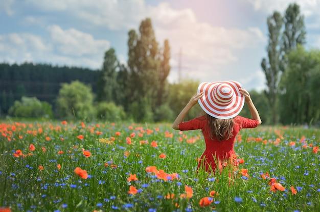 Jonge vrouw in strohoed op het gebied van de papaverbloem, zomer