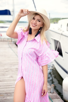 Jonge vrouw in strooien hoed en roze jurk rusten in de zomer op de pier