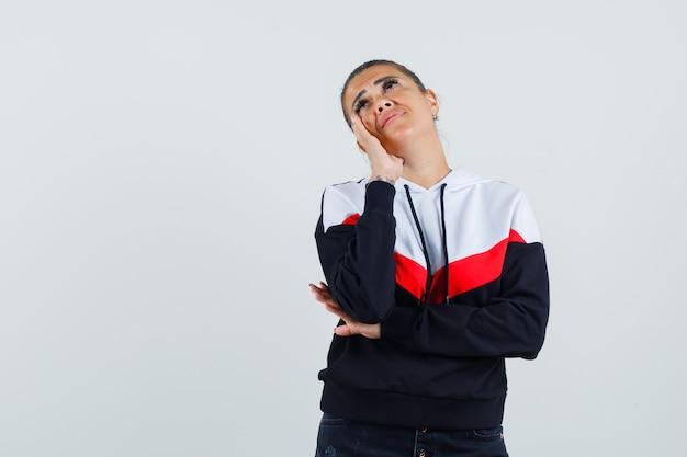 Jonge vrouw in sweater en zwarte jeans die wang op palm leunen en over iets nadenken en peinzend, vooraanzicht kijken.