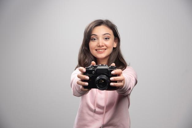 Jonge vrouw in sweatshirt met haar camera.