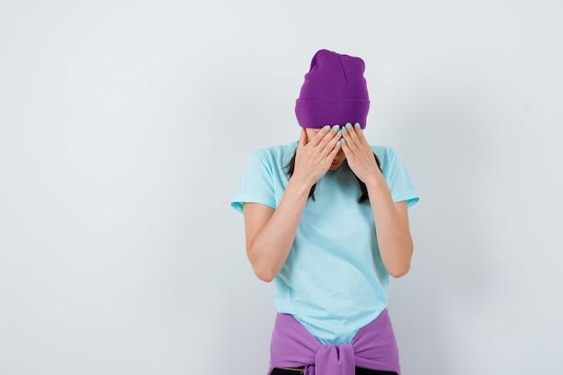 Jonge vrouw in t-shirt, beanie die hoofd naar beneden buigt, gezicht bedekt met handen en depressief kijkt, vooraanzicht.