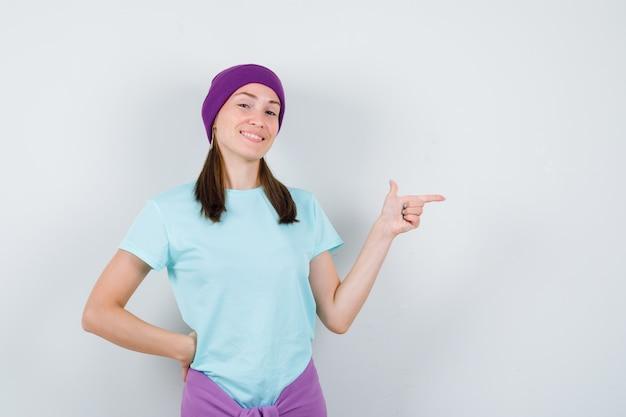 Jonge vrouw in t-shirt, beanie die naar rechts wijst, hand op taille houdt en er vrolijk uitziet, vooraanzicht.