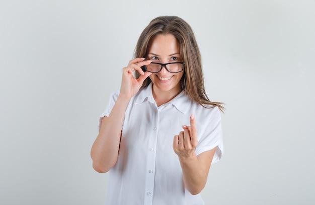 Jonge vrouw in t-shirt, bril die 'kom hier'-gebaar wenkt en er vrolijk uitziet