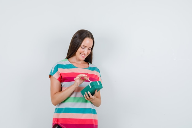 Jonge vrouw in t-shirt, broek die giftdoos houdt en blij, vooraanzicht kijkt. Gratis Foto