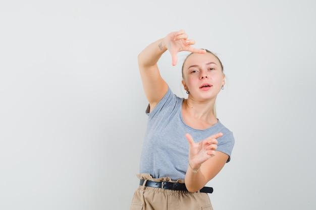 Jonge vrouw in t-shirt, broek frame gebaar maken en op zoek dartel, vooraanzicht.