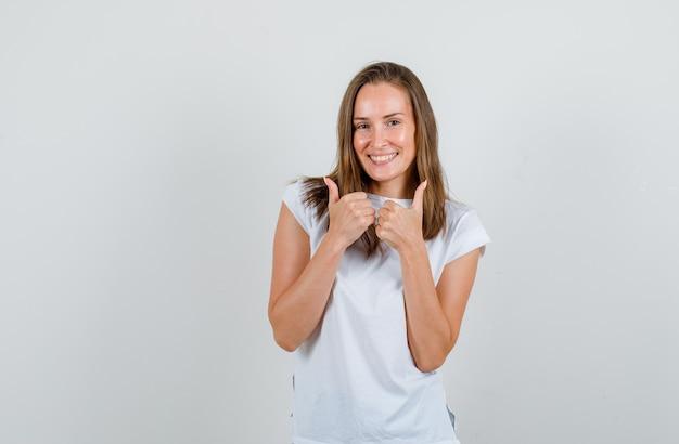 Jonge vrouw in t-shirt duimen opdagen en gelukkig kijken