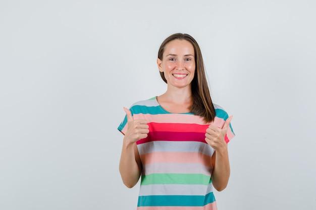 Jonge vrouw in t-shirt duimen opdagen en op zoek vrolijk, vooraanzicht.