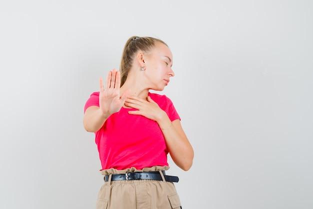 Jonge vrouw in t-shirt en broek die stopgebaar toont en verveeld kijkt