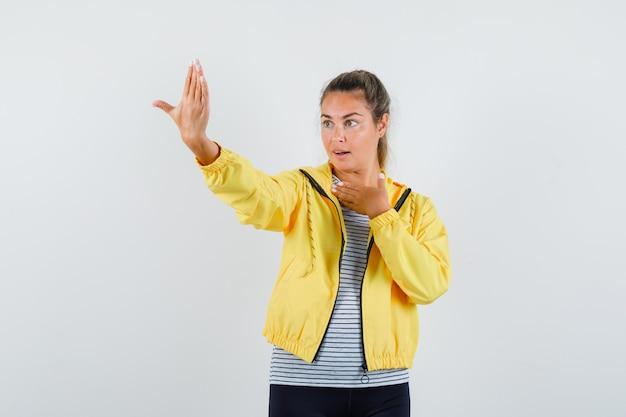 Jonge vrouw in t-shirt, jas die doet alsof ze poseert terwijl ze selfie neemt en op zoek is naar elegant, vooraanzicht.