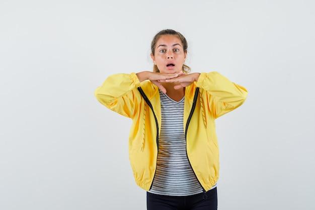 Jonge vrouw in t-shirt, jas die kin op handen steunt en nieuwsgierig, vooraanzicht kijkt.