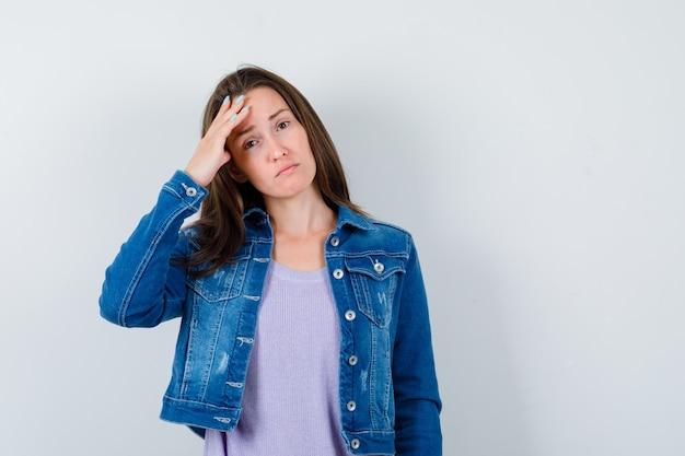 Jonge vrouw in t-shirt, jas die lijdt aan hoofdpijn en er verdrietig uitziet, vooraanzicht.
